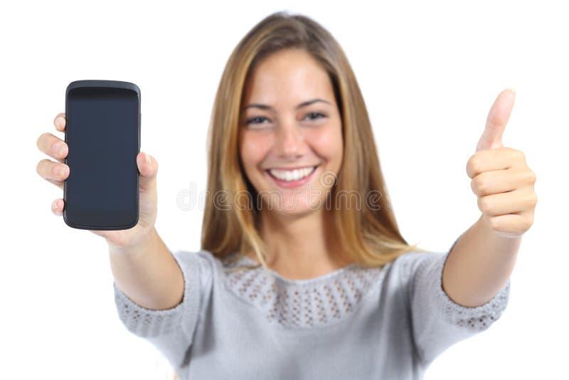 Härlig kvinna som visar en smartphone med tummen upp royaltyfri bild