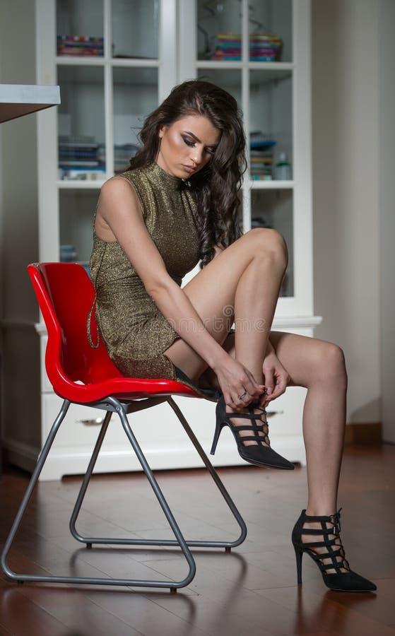 Härlig kvinna som visar henne ben som sätter på eller av tar svartskor för höga häl Bärande klänning för sinnlig attraktiv ung fl royaltyfri fotografi