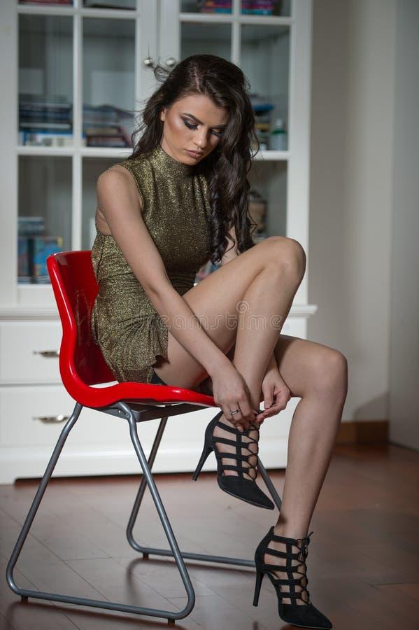 Härlig kvinna som visar henne ben som sätter på eller av tar svartskor för höga häl Bärande klänning för sinnlig attraktiv ung fl royaltyfri bild