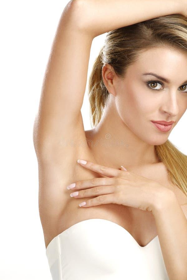 Härlig kvinna som visar hennes perfekt rakade armhåla royaltyfri foto