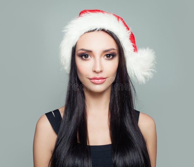 Härlig kvinnabrunett i jultomten hatt, julstående royaltyfri bild