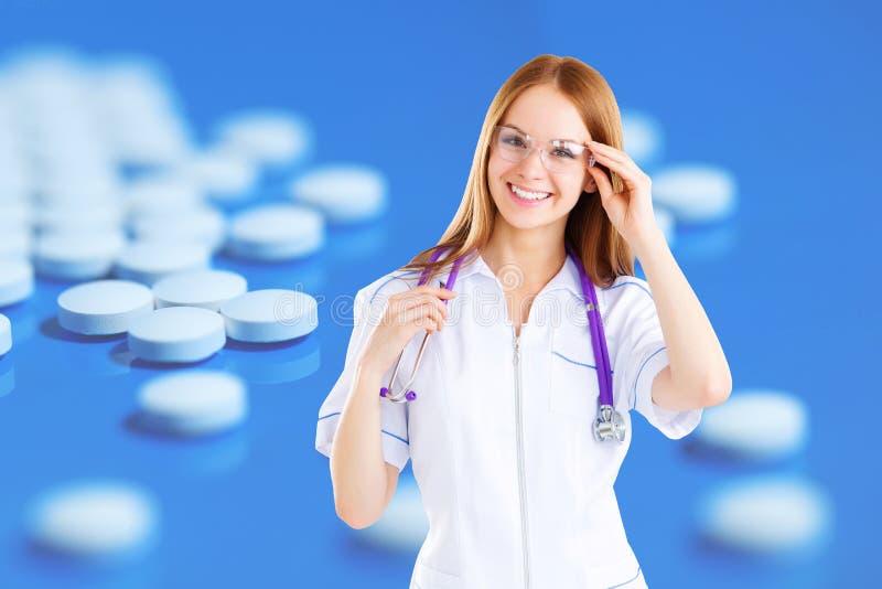 Härlig kvinnadoktor med den elektroniska minnestavlan mot bakgrunden av medicinska preventivpillerar royaltyfria bilder