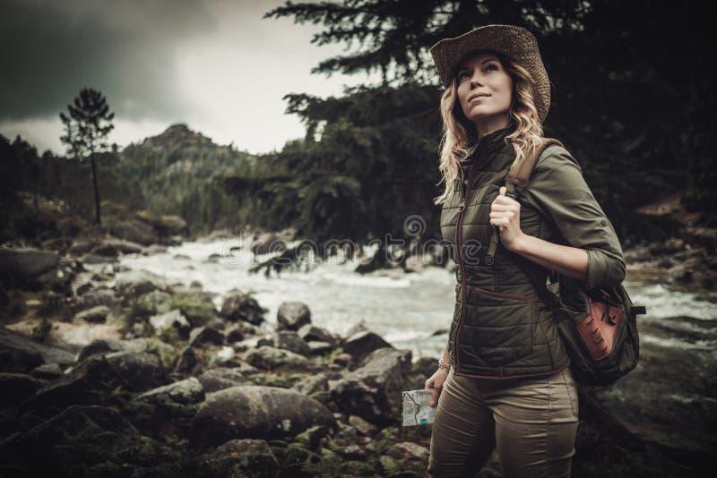 Härlig kvinnafotvandrare nära den lösa bergfloden arkivbild