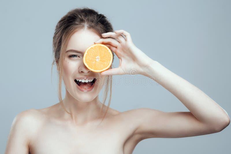 Härlig kvinnaframsida med den saftiga apelsinen på grå bakgrund Naturlig skönhet och brunnsort royaltyfri bild