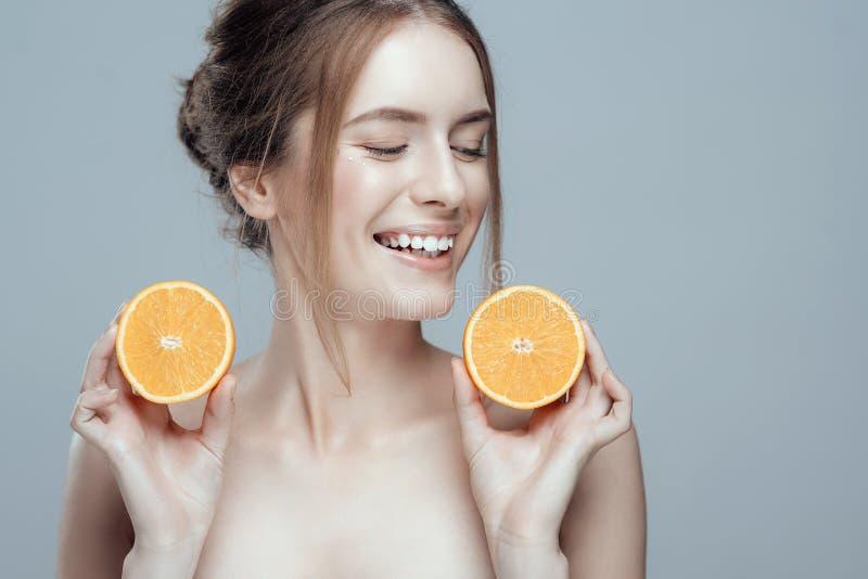 Härlig kvinnaframsida med den saftiga apelsinen på grå bakgrund Naturlig skönhet och brunnsort royaltyfria bilder