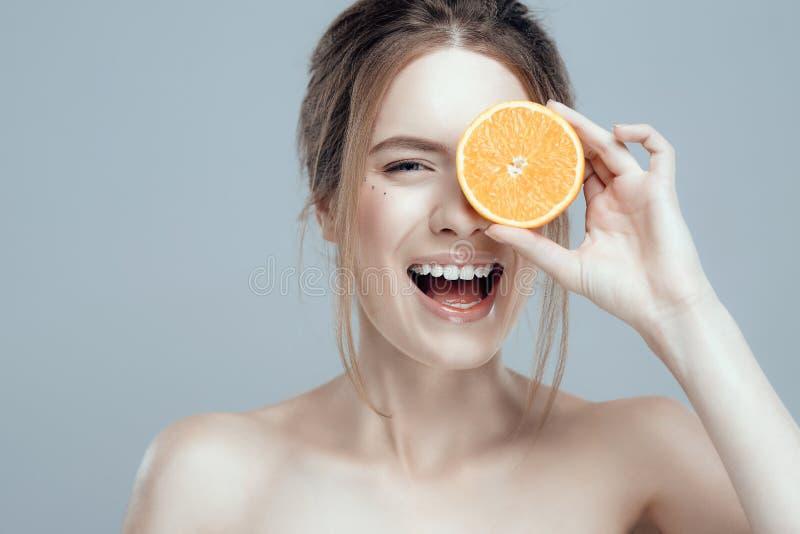 Härlig kvinnaframsida med den saftiga apelsinen på grå bakgrund Naturlig skönhet och brunnsort fotografering för bildbyråer