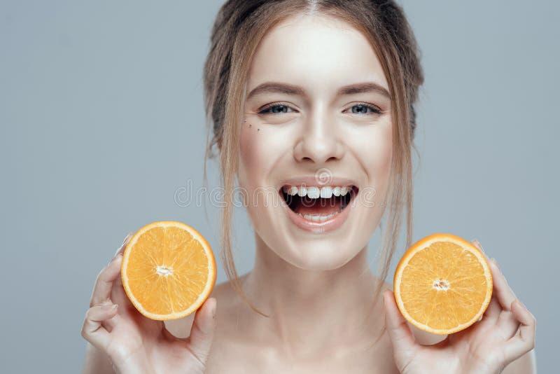 Härlig kvinnaframsida med den saftiga apelsinen på grå bakgrund Naturlig skönhet och brunnsort arkivbilder