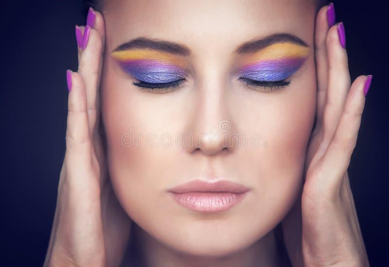 Härlig kvinnaframsida med färgrik makeup arkivbild