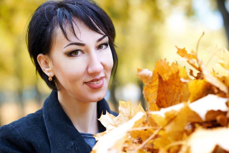 Härlig kvinnaframsidacloseup med handfullgulingsidor i den utomhus- hösten, träd på bakgrund, nedgångsäsong arkivbild
