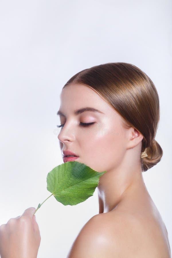 Härlig kvinnaframsidastående med det gröna bladbegreppet för hudomsorg eller organiska skönhetsmedel Hon är rädd arkivbild