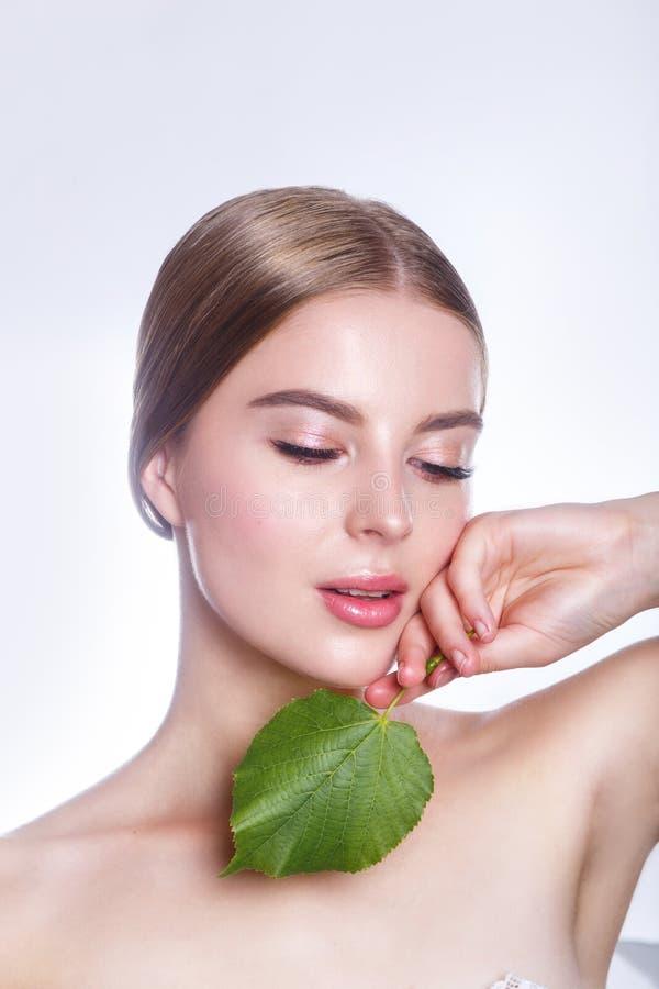 Härlig kvinnaframsidastående med det gröna bladbegreppet för hudomsorg eller organiska skönhetsmedel Hon är rädd arkivbilder