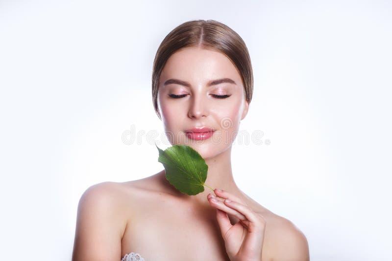 Härlig kvinnaframsidastående med det gröna bladbegreppet för hudomsorg eller organiska skönhetsmedel Hon är rädd arkivfoto
