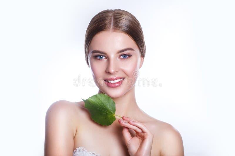 Härlig kvinnaframsidastående med det gröna bladbegreppet för hudomsorg eller organiska skönhetsmedel Hon är rädd arkivfoton
