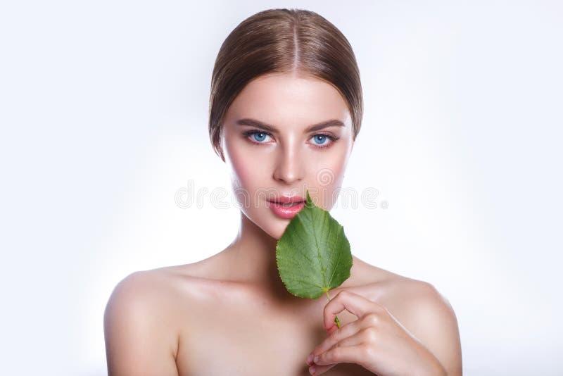 Härlig kvinnaframsidastående med det gröna bladbegreppet för hudomsorg eller organiska skönhetsmedel Hon är rädd royaltyfri foto