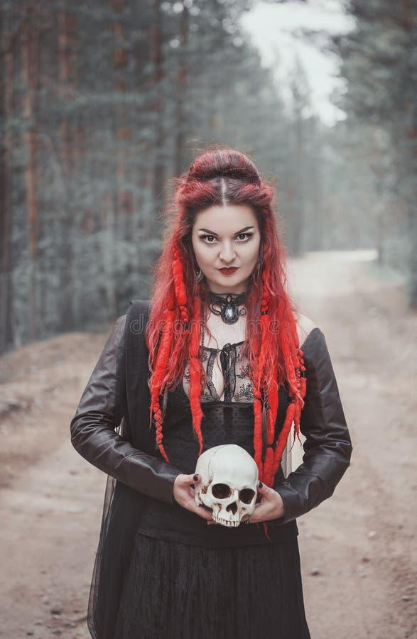 Härlig kvinnahäxa med rött hår och skallen i händer i foen fotografering för bildbyråer
