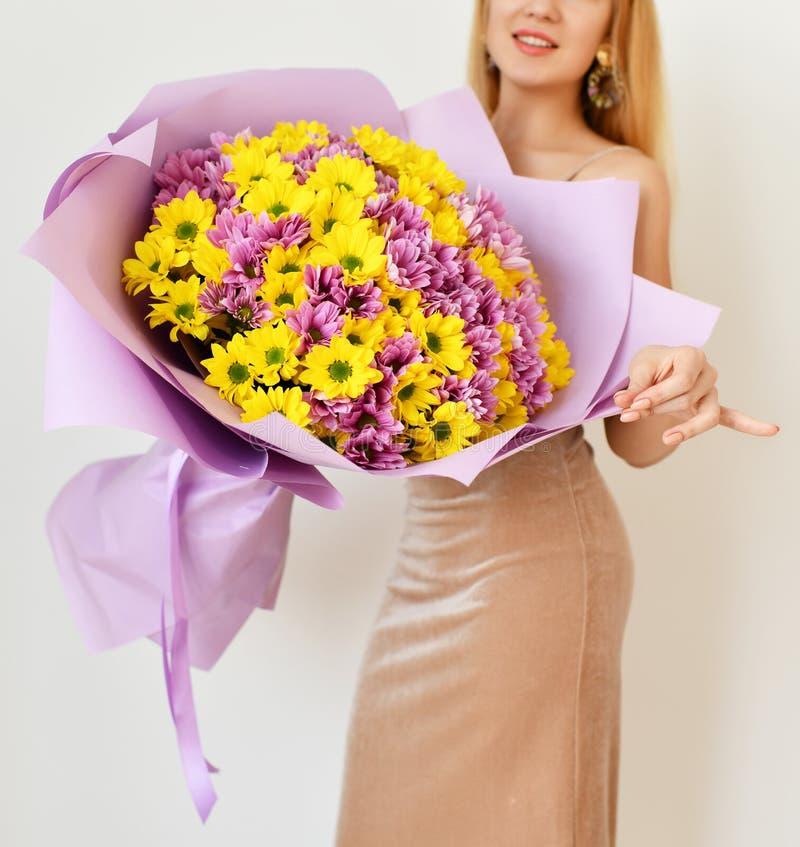 Härlig kvinnahållbukett av krysantemumblommor guling och lilor på vit arkivfoton
