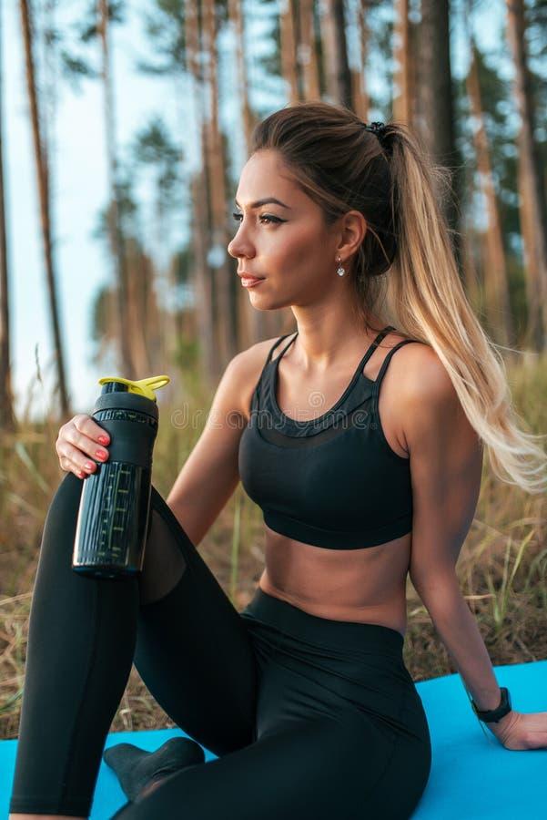 Härlig kvinnaidrottsman nen, övande yoga för flicka på filten i skogen som vilar med en flaska av shaker med proteinvatten arkivfoton