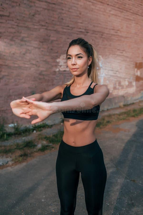 Härlig kvinnaidrottsman nen, flicka som gör gymnastik som sträcker på muskler, utbildande böjlighet och plasticitet, i staden royaltyfri foto
