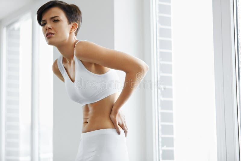 Härlig kvinnakänsla smärtar i baksida, ryggvärk Vård- fråga arkivfoto