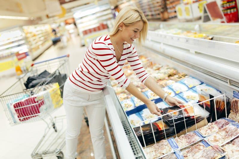Härlig kvinnaköpandemat i supermarket royaltyfri bild