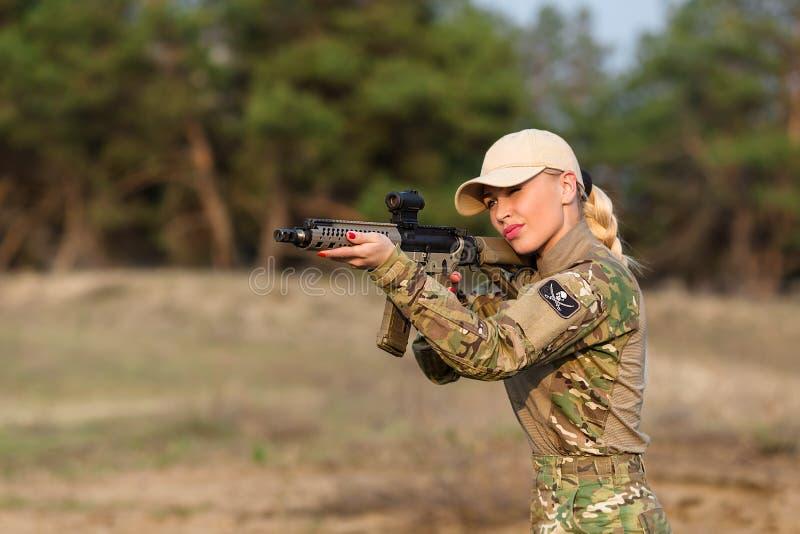 Härlig kvinnakommandosoldat med geväret i kamouflage arkivfoton