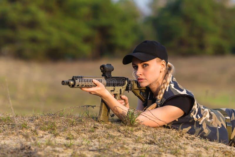Härlig kvinnakommandosoldat med geväret i kamouflage royaltyfri bild