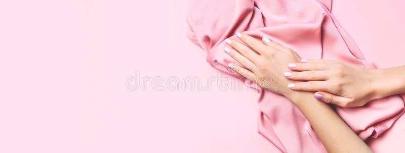Härlig kvinnamanikyr på idérik rosa bakgrund med siden- tyg Minimalist trend royaltyfri fotografi