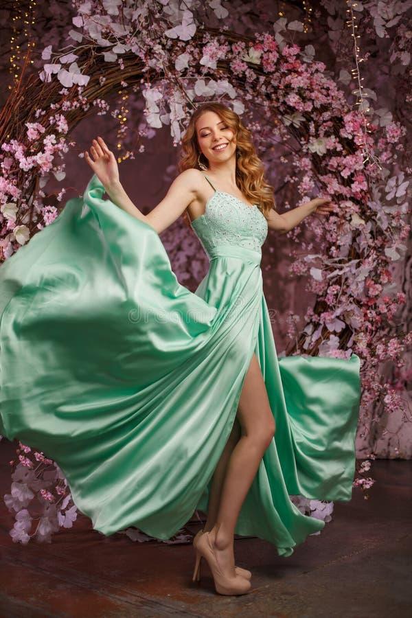 Härlig kvinnamodell i enfärgad klänning på en blommig vårbakgrund Skönhetflicka med en bedöva makeup och frisyr arkivbild