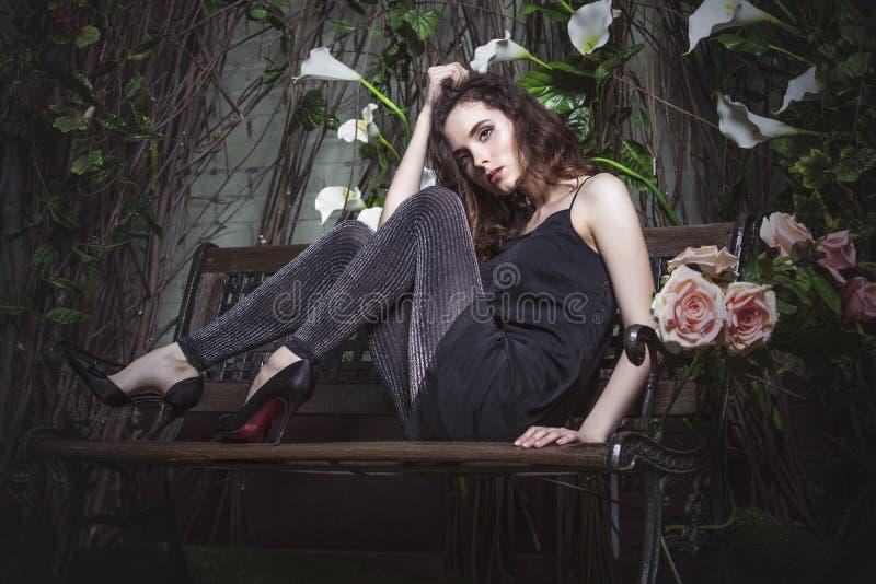 Härlig kvinnamodell i nattträdgården i stilfull klänningtunika royaltyfri foto