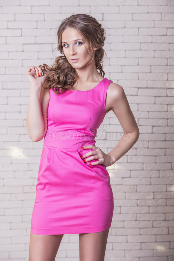 Härlig kvinnamodell i rosa kort klänning mot en vit vägg fotografering för bildbyråer