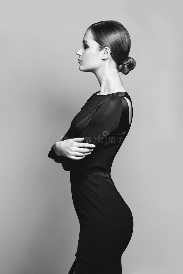 Härlig kvinnamodell som poserar i elegant klänning i studion arkivbild