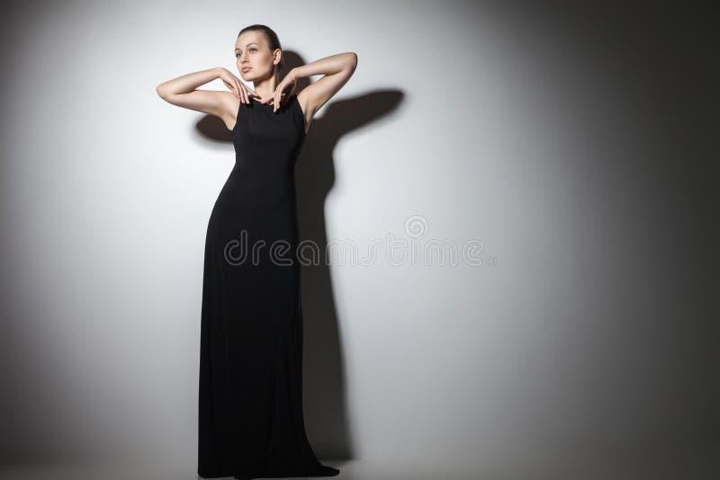 Härlig kvinnamodell som poserar i elegant svart klänning royaltyfri bild