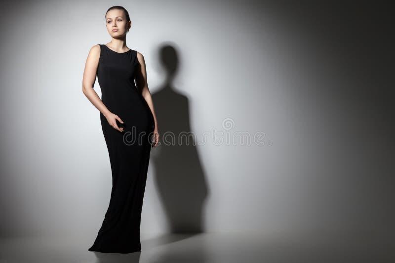 Härlig kvinnamodell som poserar i elegant svart klänning arkivfoto