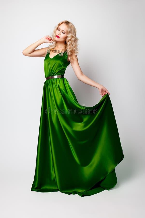 Härlig kvinnamodell som poserar i grön klänning arkivfoton