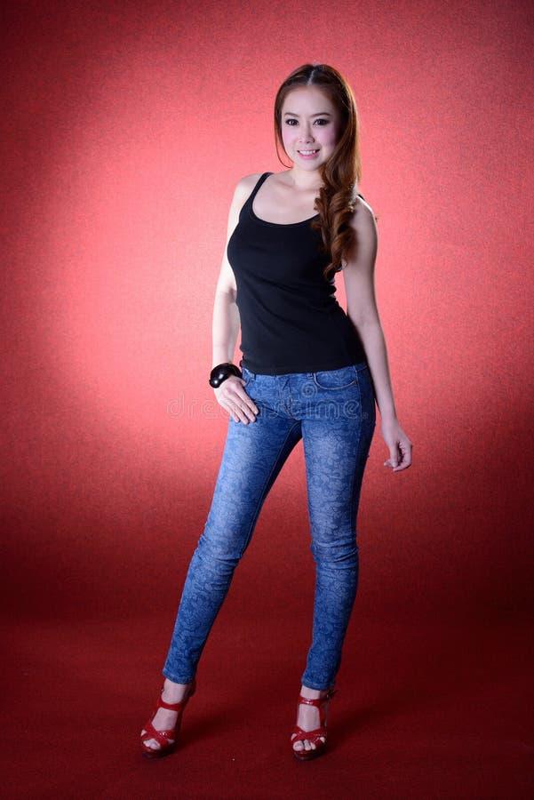 Härlig kvinnamodell som poserar på studion i de ljusa exponeringarna arkivbilder