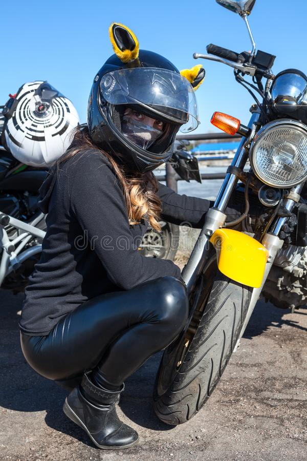 Härlig kvinnamotorcyklist som sitter nära billyktan av motorcykeln, klädd hjälm med gula öron arkivbild