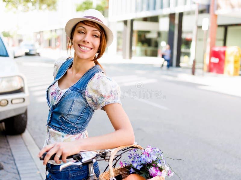 Härlig kvinnaridning på cykeln arkivfoton