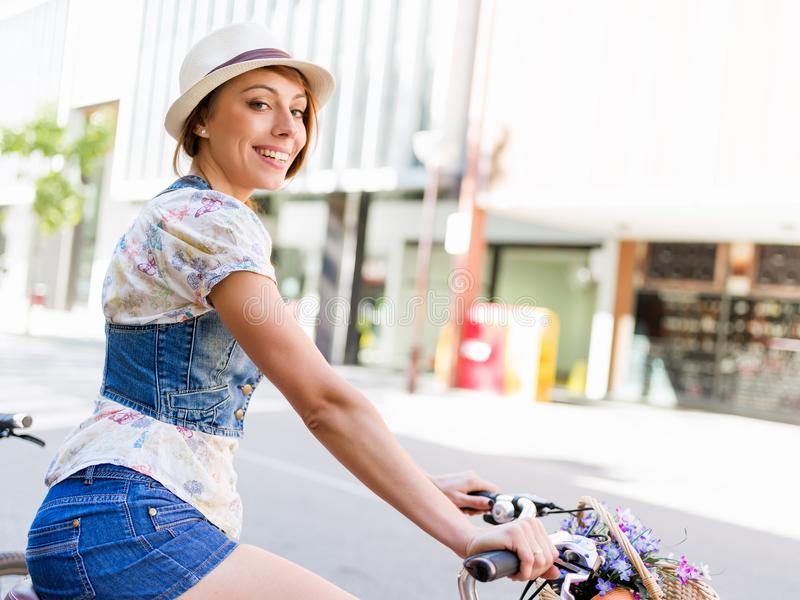 Härlig kvinnaridning på cykeln arkivbilder