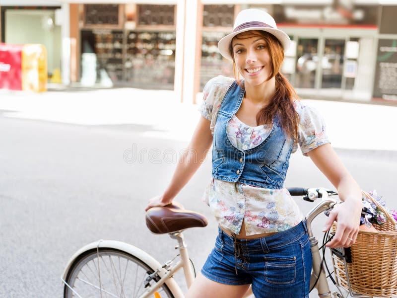 Härlig kvinnaridning på cykeln arkivfoto