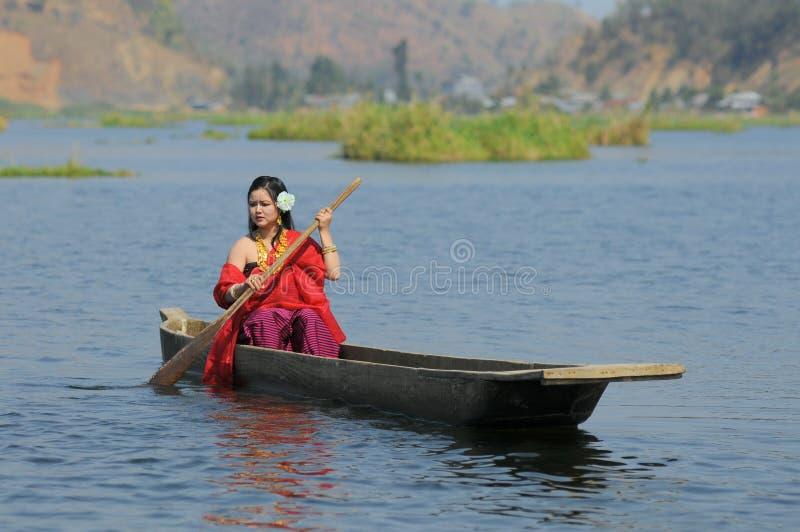 Härlig kvinnaroddkanot i sjön arkivbilder