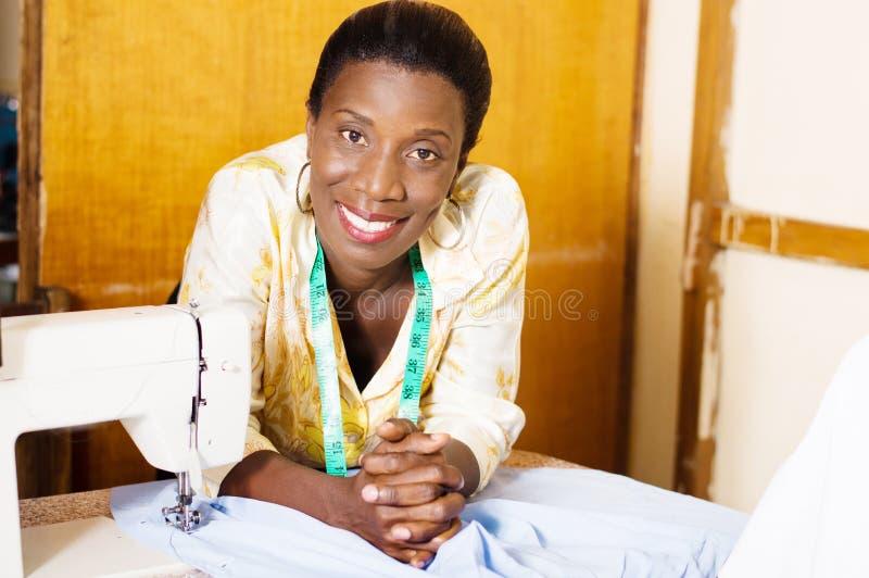 Härlig kvinnasömmerska som ler att luta på tabellen av hennes symaskin royaltyfri bild