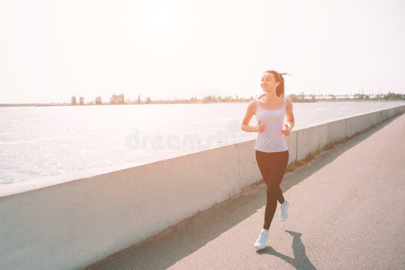 Härlig kvinnaspring under solnedgång Ung konditionmodell nära sjösidan Iklädd sportswear royaltyfria bilder