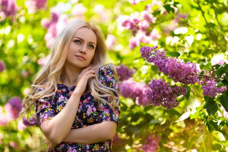 Härlig kvinnastående i lila trädblommor royaltyfri foto