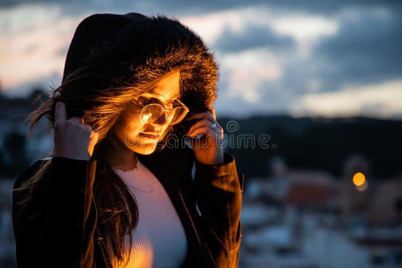 Härlig kvinnastående som göras ljusare av orange ljus royaltyfri fotografi