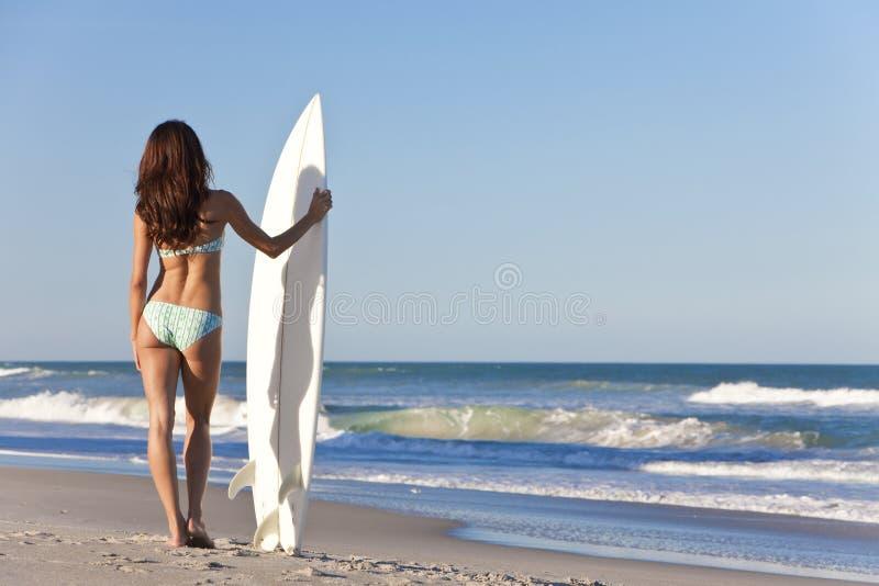 Härlig kvinnasurfare i bikinisurfingbrädastrand royaltyfria bilder