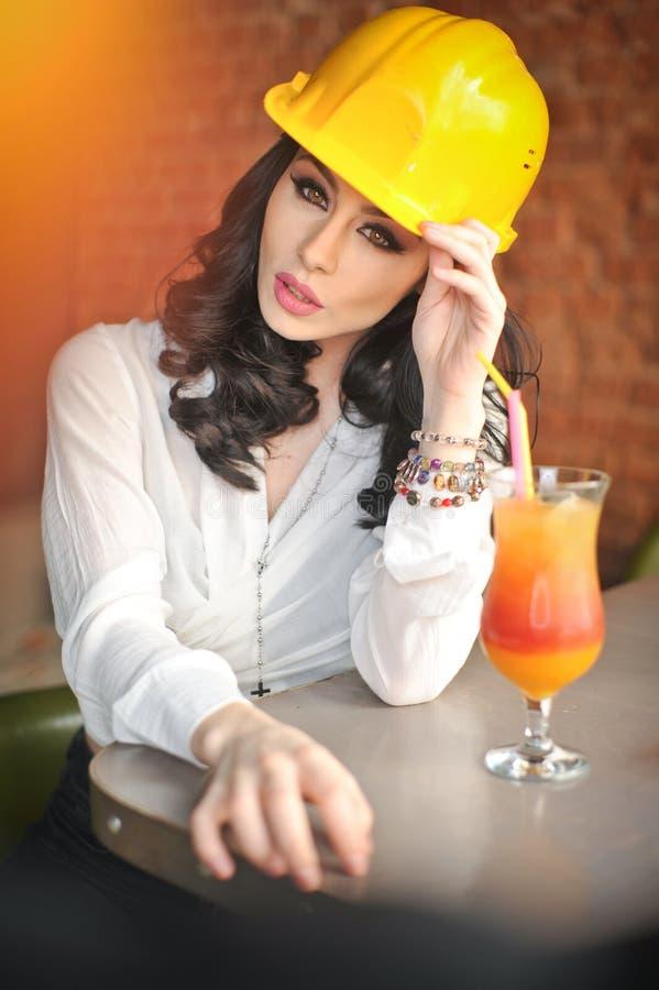 Härlig kvinnaväg-och vattenbyggnadsingenjör med den gula hjälmen som framme tar ett avbrott av orange fruktsaft Ung kvinnlig arki arkivbild
