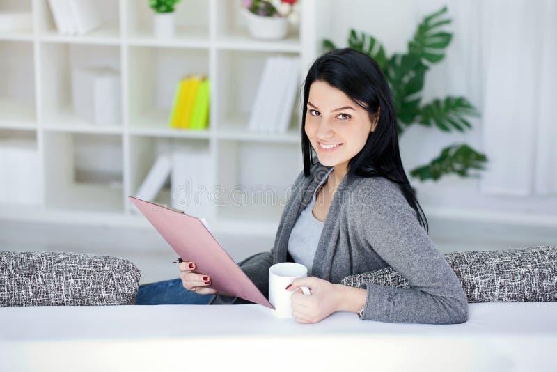 Härlig kvinnawriting i en anteckningsbok royaltyfri fotografi
