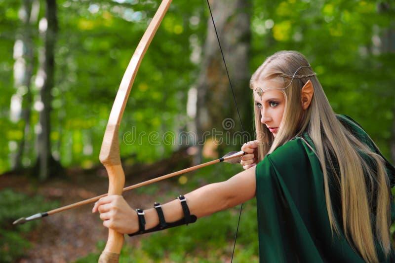 Härlig kvinnlig älvabågskytt i skogjakten med en pilbåge fotografering för bildbyråer
