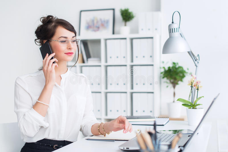 Härlig kvinnlig assistent som kallar genom att använda mobiltelefonen Ung kontorsarbetare som talar på mobiltelefonen som har aff arkivfoto