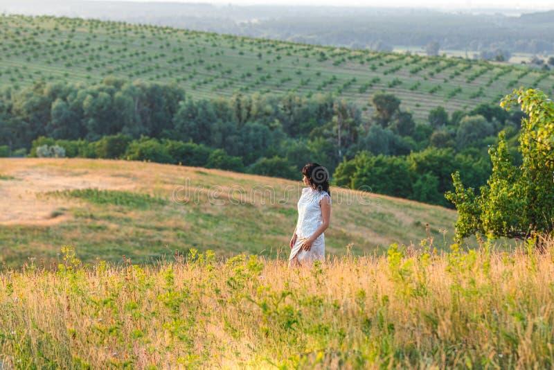 Härlig kvinnlig brunett för gullig lycklig romantiker på de gröna kullarna för sommar royaltyfria bilder